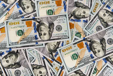 Closeup of pile of one hundred dollar bills, colorful money background
