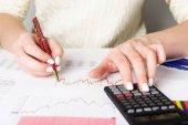 Fotografie obchodní analytik pracovní - ruce s perem, kalkulačka, list a graf