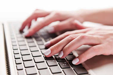 Close-up of typing female hands on keyboard of computer