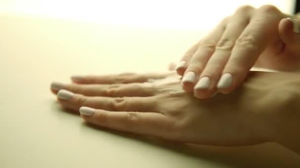 krásná žena rukou s použitím krém na pleť, manikúru detail
