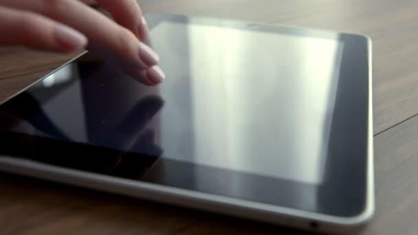 Frauenhand mit Maniküre-Scrollen auf Tablet-PC