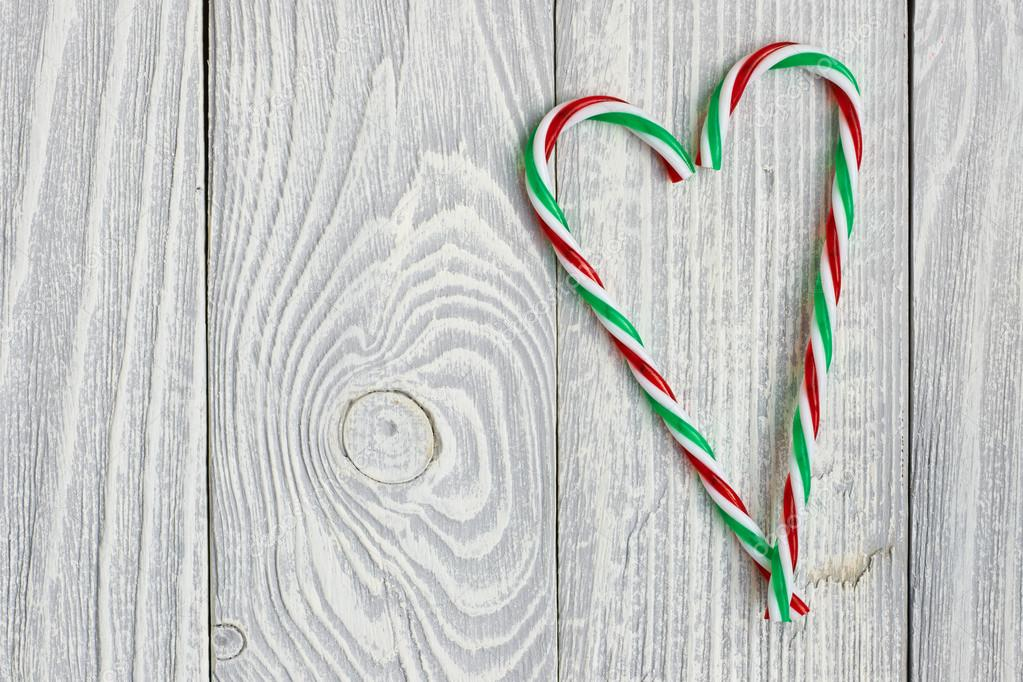 Christmas candy canes on white wooden background