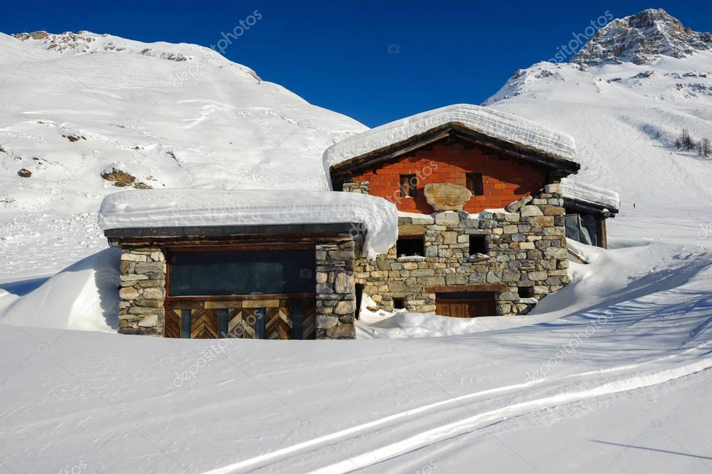 Alpine winter mountain landscape with chalet