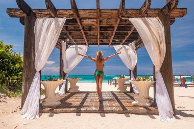 Woman at caribbean beach with pergola