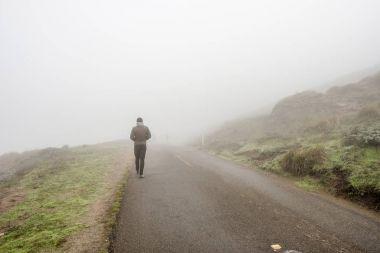 man walking through fog