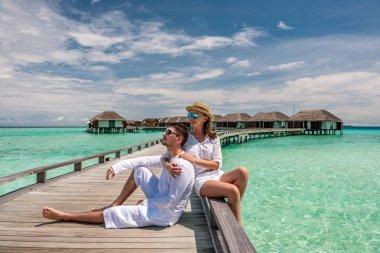 Couple on tropical beach pier