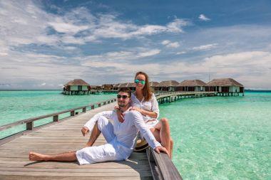 Couple on a beach jetty at Maldives