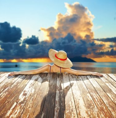 Woman in hat relaxing at beach