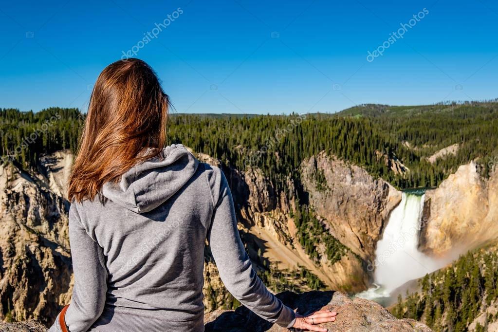 Tourist overlooking waterfall in Yellowstone