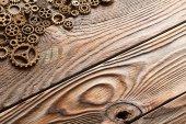 Various metal cogwheels and gear wheels over wooden background