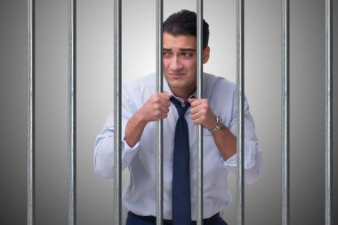 Young businessman behind the bars in prison