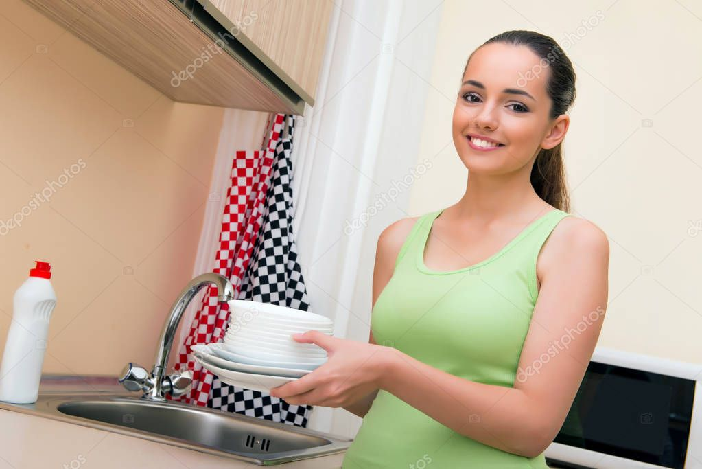 Young wife woman washing dishes in kitchen