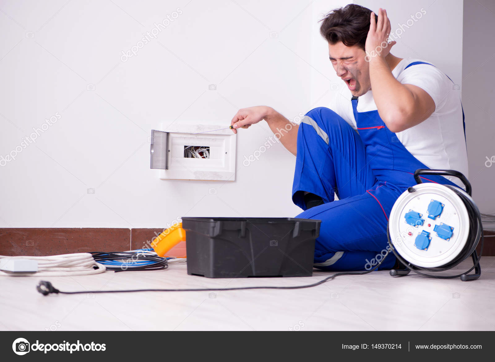 Lustige junge Elektriker an Steckdose zu Hause arbeiten — Stockfoto ...