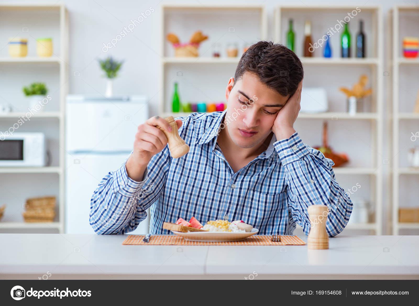 Pranzo Per Marito : Giovane marito mangiare cibo insipido a casa per il pranzo u2014 foto