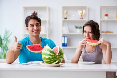 Man and woman eating watermelon at home