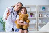 Ärztin untersucht kleines süßes Mädchen mit Spielzeugbär