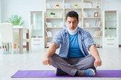 Muž s krku poranění meditaci doma na podlaze