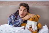 Fotografie Kranker Mann mit Grippe im Bett