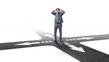 Young businessman at crossroads in uncertainty concept stock vector