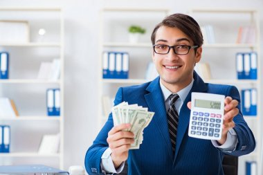 Accountant calculating dollars with calculator in office