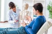 Doktor zobrazující typ zranění na kostře pacienta