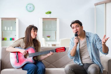 Young family singing and playing music at home
