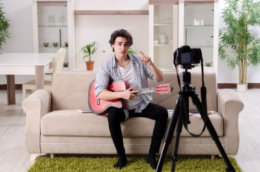 Young guitar player recording video for his blog