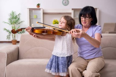 Old lady teaching little girl to play violin