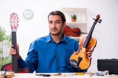 Young male repairman repairing musical instruments