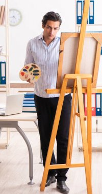 The young handsome employee enjoying painting at the office stock vector