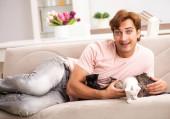 Fotografie Junger Mann spielt zu Hause mit Kätzchen