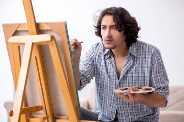 The young handsome man enjoying painting at home stock vector