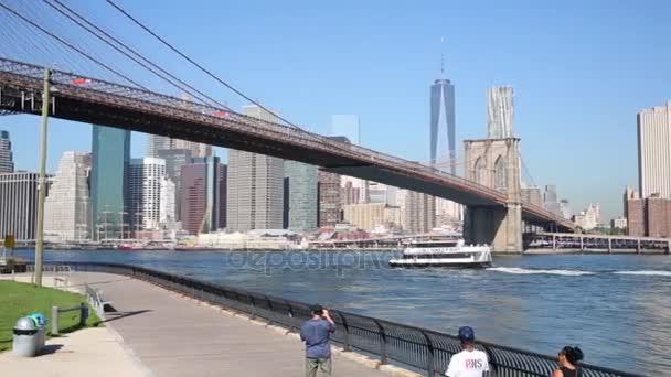 Lidé chodí na nábřeží poblíž Brooklynský most v New Yorku
