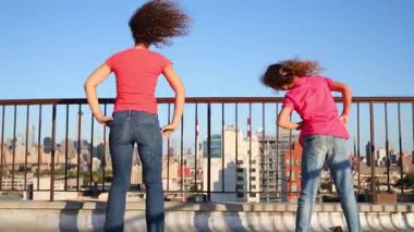 Mother and daughter do exercises on roof in New York