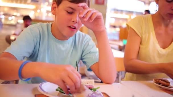 Donna e ragazzo mangiare deliziosi panini