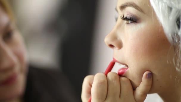 Make-up-Artist malt mit Rotstift Modell Oberlippe