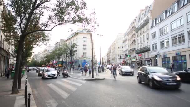 Ulice s pohyblivými auta, cyklisty, obchody v Paříži