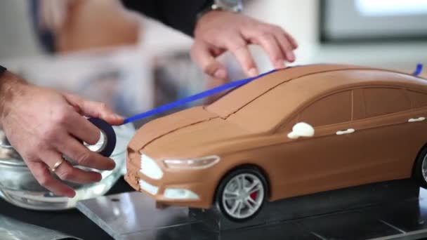 man sticking tape to scale car