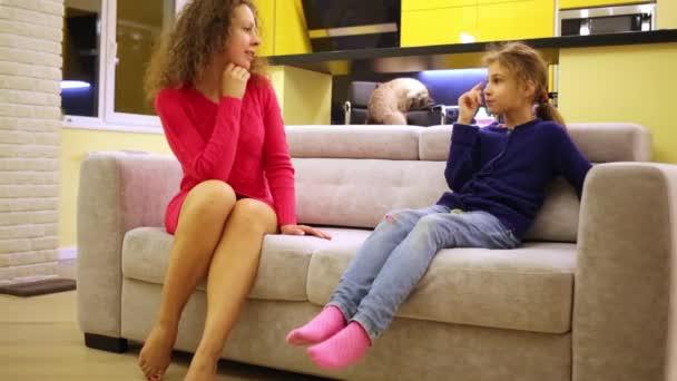 Frau und Mädchen reden auf Sofa sitzend