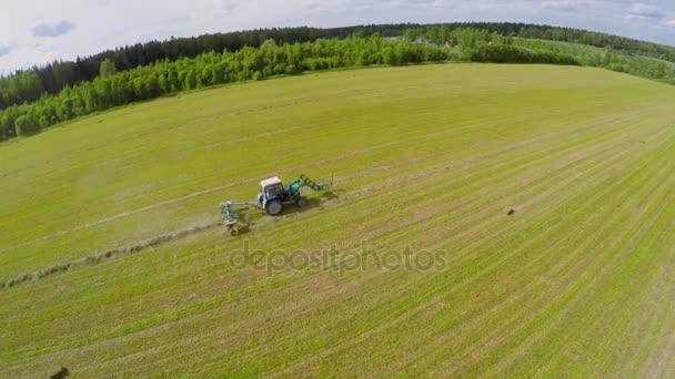 Traktor na poli nedaleko lesa shromažďuje seno