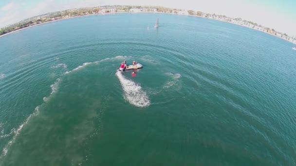 Lidé jezdí na waterbikes poblíž křídlo člun