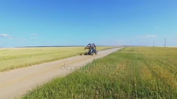 Jízda traktorem po silnici přes rue pole