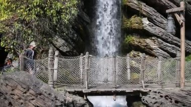 Žena s dětmi jít na dřevěný most u vodopádu