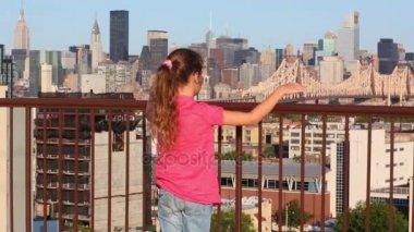 girl looking at Queensboro bridge from roof in New York
