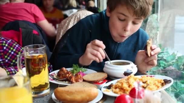 Junge isst Suppe im Café am Tisch