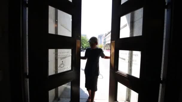 Junge öffnet und schließt Türen aus Holz