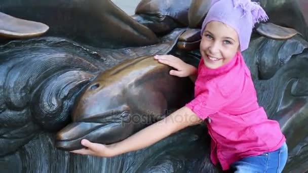 lány jelent delfin fém utcai szobor közelében