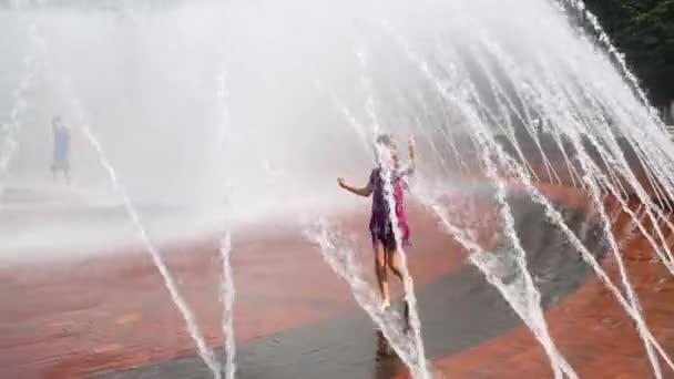 dívka hraje uvnitř fontány na ulici
