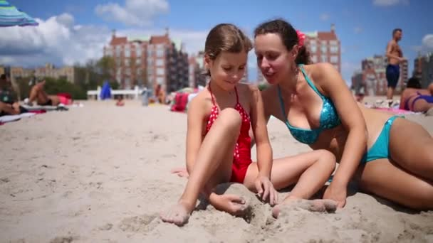Mother kisses her daughter on beach