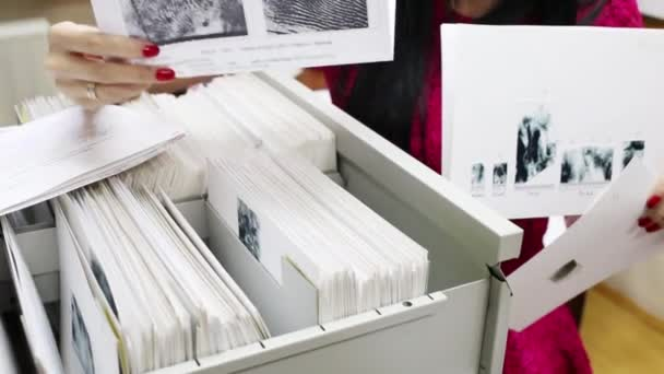 Female take out folders with fingerprints of criminals